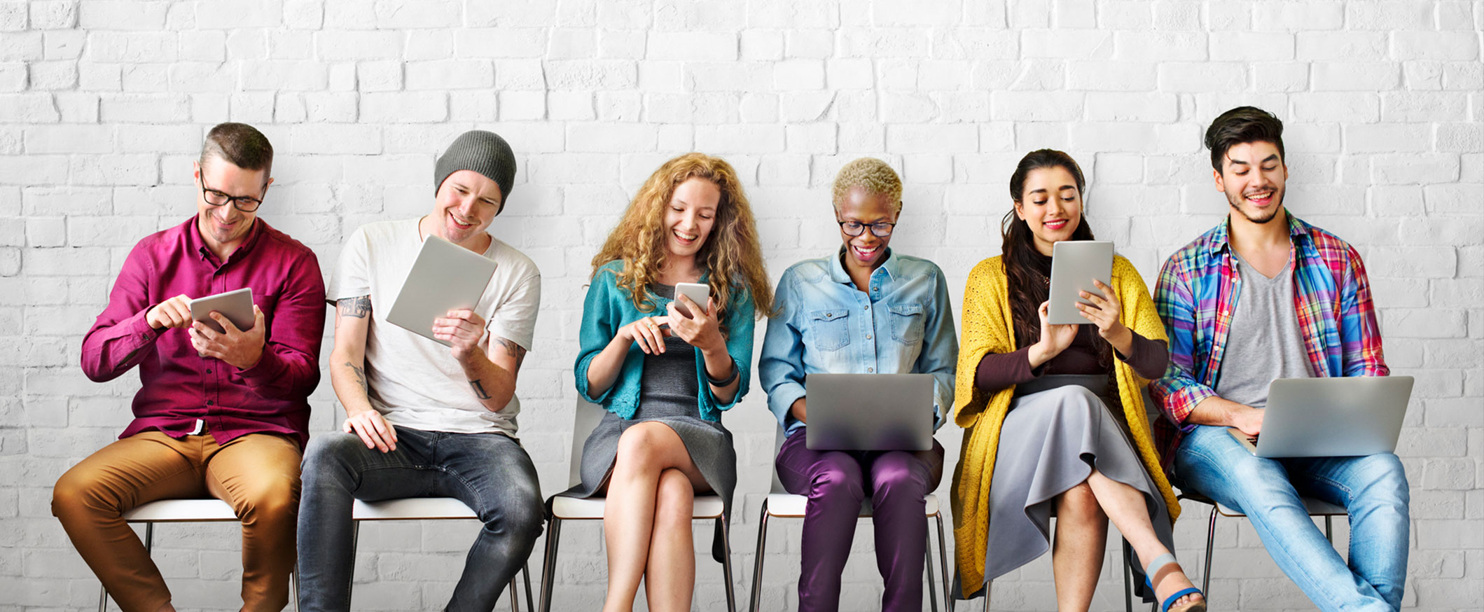 row of young people using mobile devices