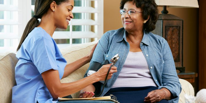 Female care worker taking blood pressure of female client