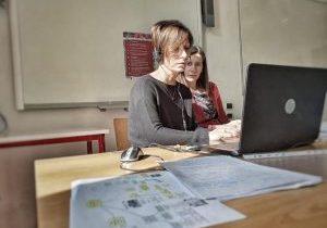 Two women working at laptop